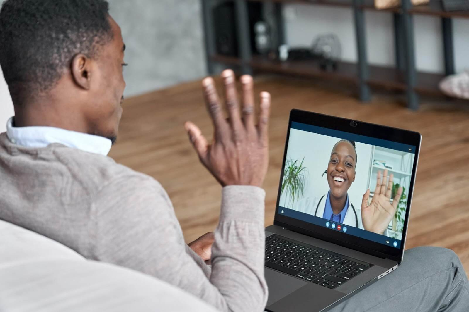 A young man using his laptop to video chat with his doctor through telehealth